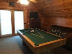 pool table in loft, the loft has a couch, TV and a few charis