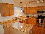 Large kitchen has granite counter tops and many kitchen accessories
