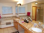 Very large master bathroom with two sinks and a granite counter top