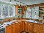 Wooden cabinetry, stained glass windows, and all of the necessary cookware make up this lively kitchen.
