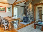 Gather around the wooden dining table next to the rock-mounted wood-burning stove to enjoy meals with your travel...