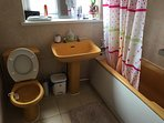 Main bathroom - toilet, sink and bath.