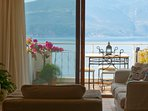 Comfortable lounge, with large glass doors, taking advantage of the stunning sea view