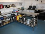 Commercial kitchen with cooker, grills, slow cookers, pots and pans