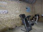 la partie 'salle de sports' de la grange (tapis de course, stepper, vélo, banc de musculation)