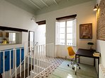 The apartment features high ceilings, exposed brick walls and traditional floor tiles.