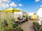 Terrace No.1 (shared). It is equipped and decorated with plants, parasol and lounge sofas.