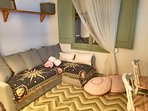 Salón con mantas y sofá cheslong  convertible en cama de matrimonio.