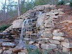 Beautiful landscaped waterfall located beside the deck with the gas fire pit.