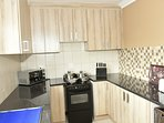 The kitchen is fully fitted with appliances and cooking utensils.