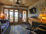 The living room features a large cable TV, wood paneling, beachy decor and comfortable seating.