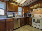 The kitchen features a dishwasher, electric oven & stove, microwave, refrigerator, blender and coffee maker.