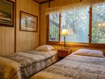 The guest bedroom has two twin-sized beds, a dresser and a nightstand with reading lamp.