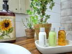 Bathroom amenities include a supply of shampoo, conditioner, body lotion, bar soap, and hand soap.