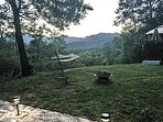 From the deck of the cottage, showing fire pit and hammock at twilight during the summer time.