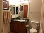 Bathroom with tub/shower, blowdryer, magnifying mirror, and  cabinet space