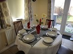 Dining table with wine glasses, napkins, table cloth and full set of dishes and cutlery at house.