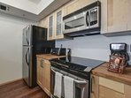 kitchen equipped with refrigerator, stove/oven, microwave, dishwasher, toaster, coffee maker and kitchen utensils