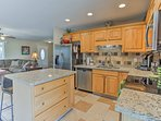 The fully equipped kitchen boasts stainless steel appliances & granite counters.