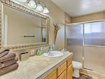 Wash up in the tile walk-in shower and single vanity found in the first bathroom.