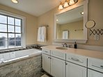 The master bathroom hosts a jetted soaking tub and Jacuzzi.