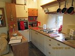 Kitchen with fridge, cooker, hob, microwave and all necessary equipment.