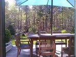 Outdoor deck overlooking back yard and garden, with dining table and chairs