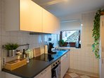 Die Küche mit Kaffeemaschine, Wasserkocher, Mikrowelle, Toaster, Backofen und Geschirrspülmaschine.