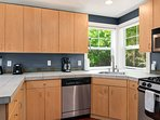 The kitchen features modern stainless steel appliances and a gas stovetop