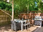 The ground floor patio has a grill and a large dining table