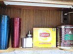 Coffee, tea, condiments, and cups. This kitchen is fully stocked.