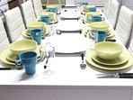 Dining table extends to accommodate dinner for 8 with plates, bowls, glasses, utensils galore