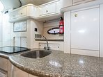 Open-plan kitchenette with 2-plate/1-plate cooker, fridge/freezer, microwave, toaster & kettle