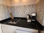 Kitchen with 2 electric hobs, kettle, toaster, microwave and Lavazza coffee machine.