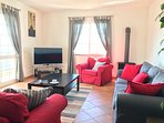 1st floor living room with new large curved screen HD TV and wood burning heater / fire.
