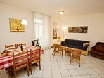 The livingroom with dinner table, sofa and wicker chairs