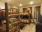 4th bedroom with two sets of twin bunks and a long sofa that can sleep a 5th person