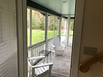 Screened in porch with stairs to the right leading upstairs.