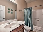 This second bathroom includes a tub/shower combo and mirrored vanity.