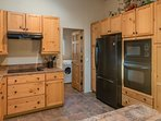 view of kitchen showing oven, microwave, glass stove top  door to laundry room