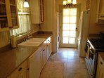 Kitchen view of large double sink and washer\/dryer combo near door