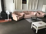 Plush, genuine leather sofa, with recliner arm chairs. slow combustion heater.