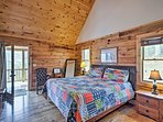 The spacious bedroom boasts a queen bed and porch access.