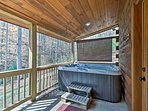 This getaway sleeps 4 guests and provides a covered porch with a hot tub.