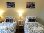 Two single beds with warm lit light and wall art!