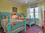 Kids will love the vibrant 4-poster twin beds in this bedroom.