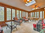 Enjoy relaxing in the sunroom with stunning views of the surrounding woods.