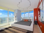 Master bedroom with ocean views, king bed, modern decor, access to balcony.