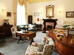 The large drawing room with an open fire feels like a family home