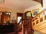 The hallway has a magnificent sweeping stairway to the floors above.